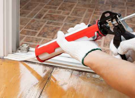 Worker applies silicone caulk on the wooden floor for sealant wa